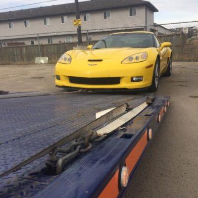 Loading a Corvette onto the single axle deck truck.