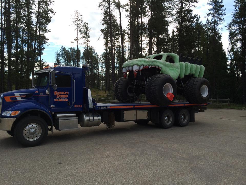 Tandem axle deck truck hauling a monster truck.