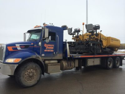Tandem axle deck truck hauling paving equipment