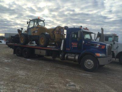 Tandem axle deck truck hauling a telehandler.