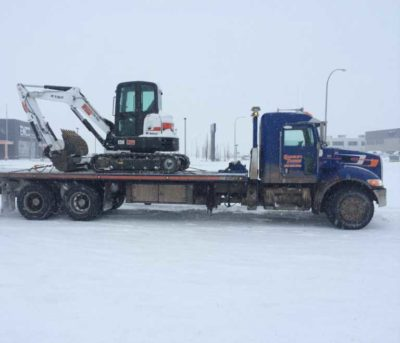 Tandem axled deck truck hauling a mini excavator