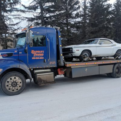Single axle deck truck hauling a 1971 Dodge Challenger.